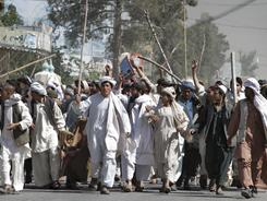 Afghan protesters walk with sticks as they carry a wounded colleague during a demonstration Saturday in Kandahar, Afghanistan. They condemned the burning of the Quran.