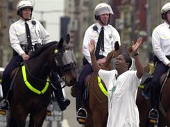 Sheryl Brown with the New Jerusalem Missionary Baptist Church prays as she stands in front of a line of mounted police officers at Central Parkway and Race Street in Cincinnati on April 11, 2001.