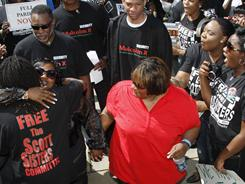 Gladys Scott, left, hugs a supporter as her sister Jamie Scott thanks the protesters who marched on their behalf Friday in Jackson, Miss.
