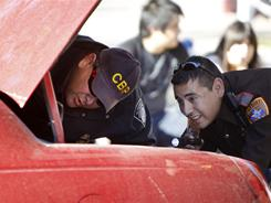 A Customs and Border Protection officer and a local sheriff's deputy check the trunk of a car heading southbound from the United States to Mexico.