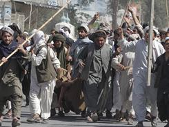 Protesters carry a wounded colleague during a demonstration to condemn the burning of a copy of the Muslim holy book by a Florida pastor in Kandahar, Afghanistan, on Saturday.