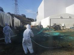Tokyo Electric Power Co., workers spray adhesive synthetic resin over the ground at the Fukushima Dai-ichi nuclear power plant in Okumamachi in a photo released April 1.
