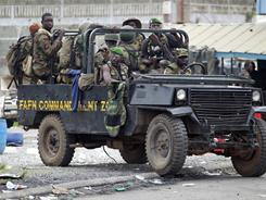 Soldiers loyal to Alassane Ouattara drive at a checkpoint at one of the principal entrances to Abidjan, Ivory Coast.