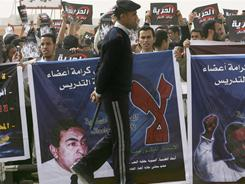 An Egyptian policeman walks  by protesters holding banners with pictures of some detained Muslim Brotherhood members. The most established fundamentalist group, the Muslim Brotherhood, has years of experience in contesting elections.