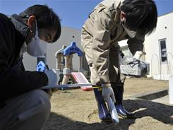 Government workers monitor radiation levels at a day care center in Iitate, Fukushima Prefecture, in northern Japan.