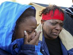 Marcie Moorer, left, whose son Alix Bonhomme III was killed during a storm along with his father Alix Bonhomme Jr., mourns with Rachel Battle, right, in Jackson, Ga., on Tuesday.