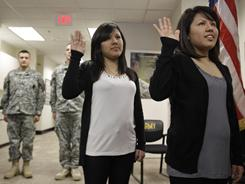 Identical twins Melissa Ventura-Benel, center, and Meilyn Ventura-Benel take the U.S. Army oath of enlistment on Feb. 4 in Hayward, Calif. Both are Peruvian and will earn their U.S. citizenship.