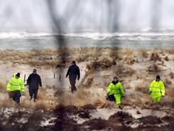 Suffolk County Police and police recruits search an area of beach Tuesday near where human remains were found in Babylon, New York.