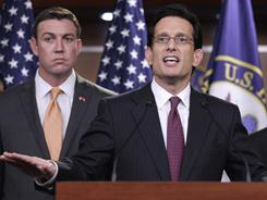 House Majority Leader Eric Cantor, flanked by Rep. Duncan Hunter, left, discusses spending cuts Thursday.