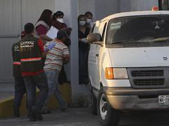 Forensic workers prepare to transfer bodies from a van Wednesday in the northern border city of Matamoros, Mexico.