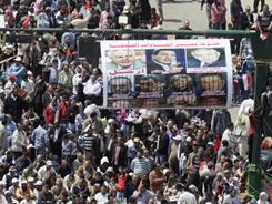 Egyptian protesters stand under a poster of former President Hosni Mubarak and some editors of governmental newspapers and magazines in Cairo's Tahrir Square on Friday.