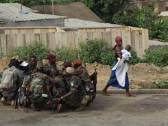 A woman walks past soldiers loyal to Alassane Ouattara in Abidjan, Ivory Coast, on Friday.