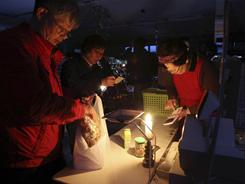 A cashier uses a calculator with candle light to see after a 7.1-magnitude aftershock quake in Japan caused blackouts.