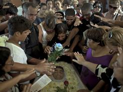 Relatives and friends pray over the body of Igor Moraes da Silva during his funeral at a cemetery in Rio de Janeiro, Brazil, on Friday.