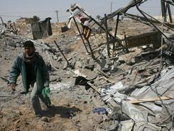 A Palestinian boy inspects the damage following an Israeli airstrike on a smuggling tunnel in Rafah, on the border between Egypt and southern Gaza Strip on Friday.