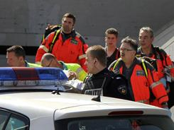 An injured person, center, is carried out of a shopping mall by an ambulance crew and emergency workers after a shooting in Alpen aan den Rijn in the Netherlands on Saturday.
