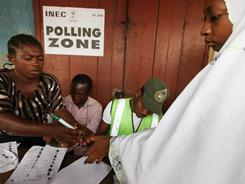 A Muslim woman has her finger inked after casting her vote Saturday at a polling station in Ibadan, Nigeria.
