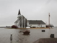A cemetery sits under flood water in the yard of a rural church April 10 near Gardner, North Dakota. The Red River crested yesterday about 25 miles south of Gardner in Fargo, North Dakato at 38.5 feet.