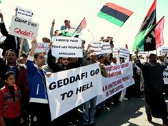 Libyan protestors wave Libya's former flags and hold banners as they demonstrate outside a hotel during a meeting between African head of states and Libyan rebel leaders, in the eastern rebel stronghold of Benghazi.