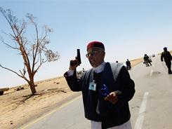 A supporter of the Libyan rebellion chants while wielding a pistol Monday as opposition fighters await a confrontation with government troops. 