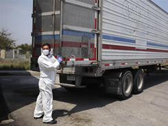 A morgue employee prepares to unload a body found in a mass grave, from a refrigerated truck in Matamoros, northern Mexico.