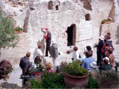 Volunteer guide Frank Runball shows a South African church group markings on the stones near the low doorway to the Garden Tomb in Jerusalem, the place many evangelical Protestants consider the authentic burying place of Jesus.