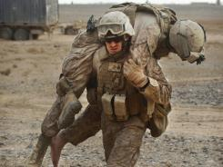 A Marine carries a wounded colleague to a medevac helicopter after their convoy hit an improvised explosive device on Jan. 27 near Marjah in Afghanistan.
