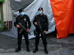 Mexico City police guard a refrigerated truck carrying bodies that were found in mass graves in northern Mexico Thursday.
