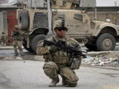 A U.S. soldier kneels as he controls the area near the scene of a suicide attack in Kandahar , Afghanistan, on Thursday.