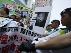 Pro-democracy protesters holding a picture of detained Chinese artist Ai Weiwei gather outside the China Liaison Office in Hong Kong on Sunday.