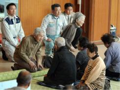 Japanese Emperor Akihito, second left, and Empress Michiko visit a shelter at Asahi city, Japan, on Thursday  in their first trip to an area hit by the March 11 earthquake.