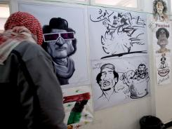A Libyan rebel looks at caricatures of Libyan leader Moammar Gadhafi in the rebel-held city of Benghazi on Thursday.