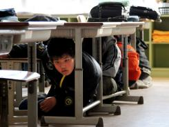 Elementary school children crouch under their desks at their school in Onagawa, Japan, on Tuesday, as a powerful aftershock hit northern Japan.