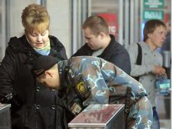 A police officer checks the belongings of a subway commuter in Minsk, days after a  blast rocked the station.