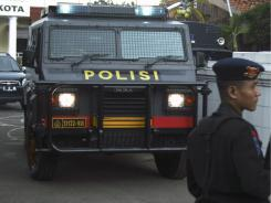 A police officer stands guards a police station Friday after a bomb went off in West Java, Indonesia.