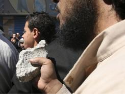 A protester holds a stone during a demonstration for extremist Salafi Muslims in  Zarqa, Jordan.