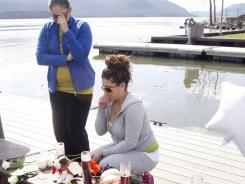 Natasha Colon, left, and Nicole Callahan, on Thursday visit a memorial at the boat ramp where Lashanda Armstrong drove her minivan into the Hudson River killing herself and three of her kids in Newburgh, N.Y.