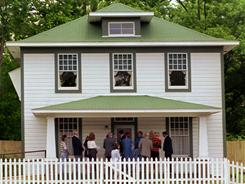 Visitors wait in line to enter President Clinton's birthplace home in Hope, Ark.