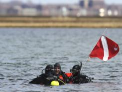 Suffolk County dive team police officers search for possible victims Thursday  near Cedar Beach, N.Y.