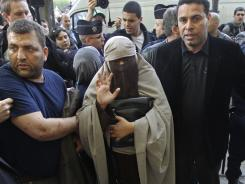 An unidentified veiled woman is taken away by police officers, flanked by her two friends, in Paris last week.
