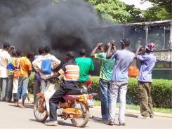 """Residents take pictures of a bus burning during a protest against soldiers by shopkeepers near the Ouagadougou """"Rood Wooko"""" great market on April 16."""