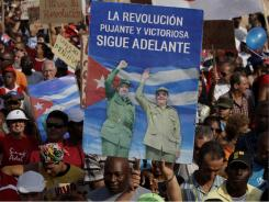 A Cuban holds up a poster with images of Cuban leader Fidel Castro and his brother, President Raul Castro, during a parade commemorating the 50th anniversary of the Bay of Pigs in Havana on Saturday.