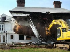 "An excavation loader is used to demolish the ""Land's End"" mansion in Sands Point, Long Island, N.Y., on Monday."