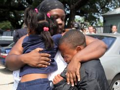 Evette Davis hugs her daughter Heaven, 5, and son Julian, 9,  after a kindergartener brought a loaded gun to his Houston elementary school Tuesday, injuring himself and two others.