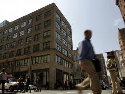 People walk by a building containing offices of PrimeTel Communications on Friday in Philadelphia.