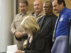 Arizona Gov. Jan Brewer signs an immigration bill on April 23, 2010.
