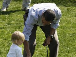 President Obama coaches a young participant in getting the scoop during last year's Easter event.