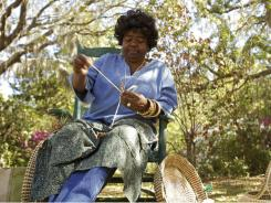 Vera Manigault, a traditional Gullah Sweet Grass Basket Weaver, starts work on a basket outside of the Gullah & O'oman Gift Shop in Pawleys Island, S.C.