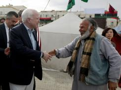 Sen John McCain shakes hands with a Libyan rebel during his tour to the rebel headquarters in their eastern stronghold city of Benghazi on Friday.