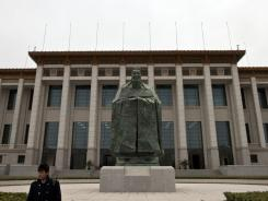 In this March 31, 2011 photo, a security guard stands near a statue of ancient Chinese philosopher Confucius in front of China's National Museum near the Tiananmen Square in Beijing, China.